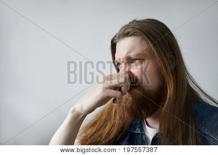 Disgusted guy with long hairstyle pinching nose with fingers because something stinks. Squeamish man trying to avoid disgusting smell of spoiled food. Bad smell situation and odor. Human reaction