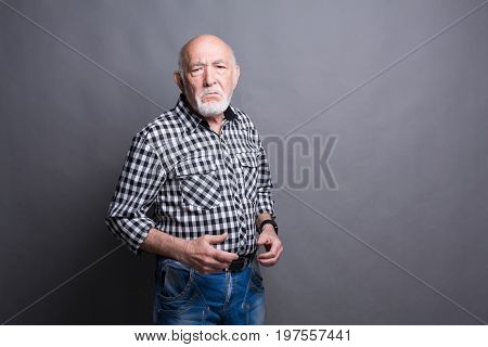 Angry senior man posing, copy space. Ready to fight mature male, gray studio background