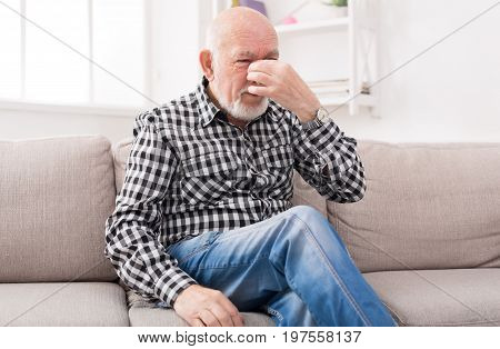 Elderly man with headache pinching back of his nose. Senior male sitting on sofa at home and suffering from migraine, copy space