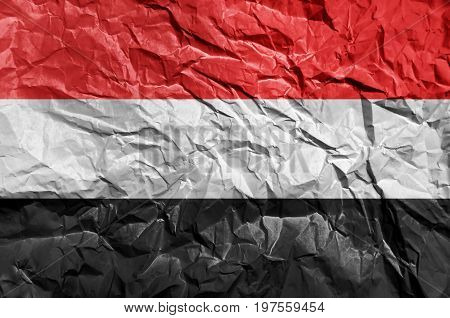 Yemen flag painted on crumpled paper background