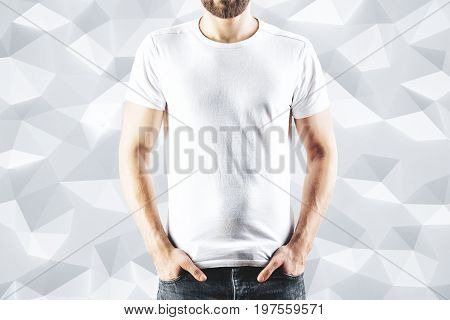 Shirt design and people concept. Close up of male in blank white t-shirt front view. Clean empty mock up template for your design. Polygonal background