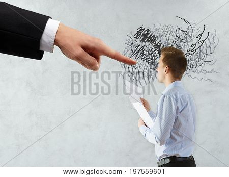 Hand pointing at thoughtful businessman with paperwork and scribble. Concrete wall background. Workload concept