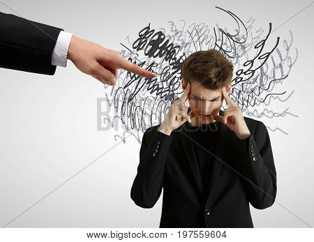 Hand pointing at pensive businessman with scribble. Gray wall background. Confusion concept