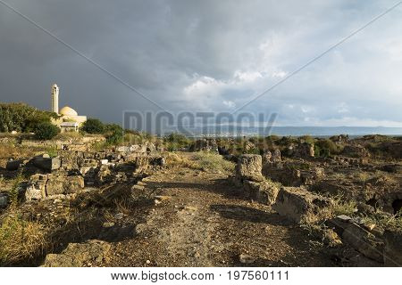 Path with sunlight during storm in ruins with mosque with dramatic cloudscape in Tyre, Sour, Lebanon