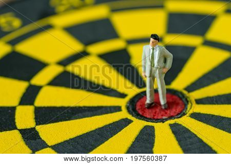 financial business goals concept as brave miniature businessman standing at the center of dartboard.