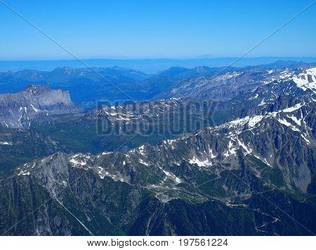 Alpine mountains range landscape in beauty French, Italian and Swiss ALPS seen from Aiguille du Midi at CHAMONIX MONT BLANC in FRANCE with clear blue sky in warm sunny summer day, EUROPE, JULY.