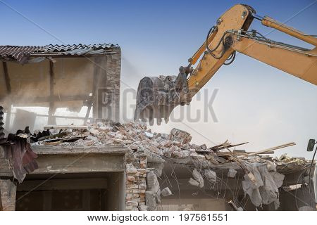 Backhoe Demolishing House