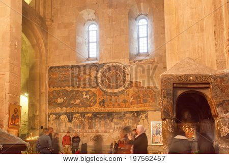 MTSKHETA, GEORGIA - OCT 13, 2016: Prayers and the old frescoes of the christian Svetitskhoveli Cathedral on October 13, 2016. Cathedral was built in 4th century. UNESCO World Heritage Site.