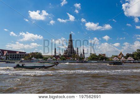 Arun Temple With Passenger Boat On Chao Phraya River In Bangkok, Thailand.