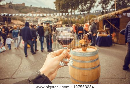 Wine glass and many people walking down the celebration streets during autumn city festival Tbilisoba. Georgia country.