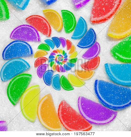 Abstract spiral fruit jelly rainbow wedges slices on white sugar sand background. Rainbow jelliy candies. Sweet fruit jelly liths. Candy dessert. Abstract food fractal Exotic sweets pattern background