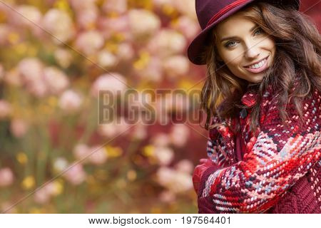 Woman in coat with hat and scarf in autumn park