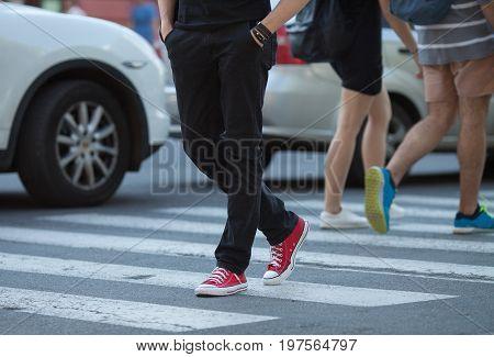 People's legs on cross walk, walking. Zebra.