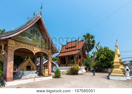 Asian style golden temples close to Wat Xieng Thong located in the city Luang Prabang Laos. Lonely tourist woman walking alone