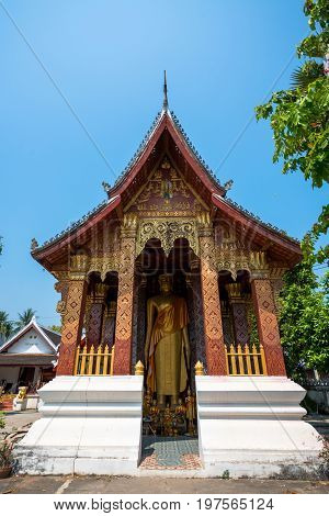 Vertical picture of small golden temple with a standing Buddha close to Wat Xieng Thong located in the city Luang Prabang Laos