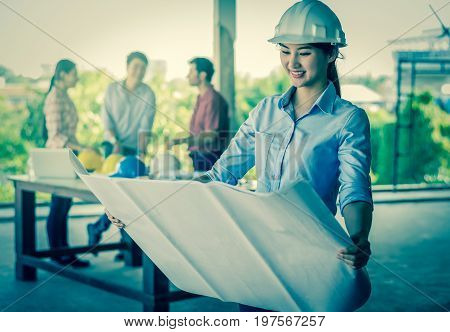 Portrait of Happy professional construction engineer woman working with the blueprint and wearing the safety helmet and glasses at the building site place background industrial engineering concept