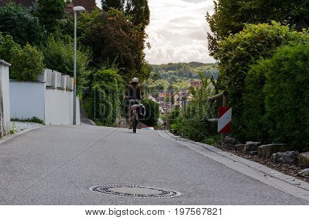 Neighborhood Landscape Rear View Biker Moving Away onto Rolling Hills Beautiful Nature