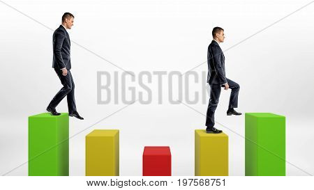 Two businessmen on white background stepping up and down green, yellow and green statistic columns. Business and success. Profit and loss. Business ups and downs.