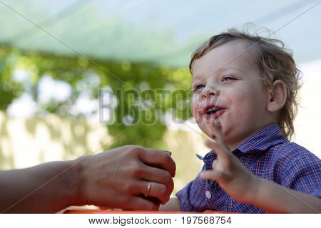 Boy drinking juice fron his mother hand