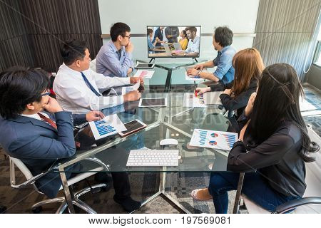 Group of asian Business team having video conference with their colleagues from another country via monitor display in the modern conference room Business people meeting concept