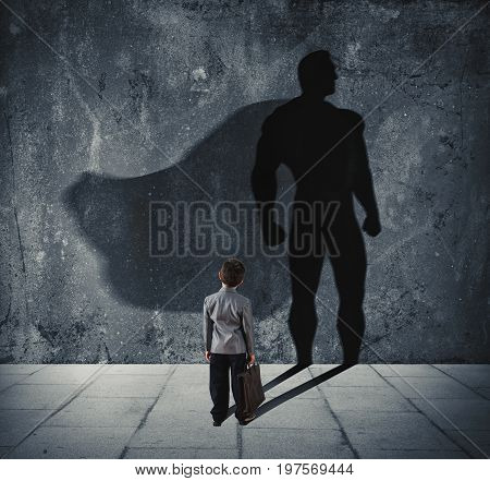 Young businessman with his shadow of big super hero on the wall. Concept of powerful small man