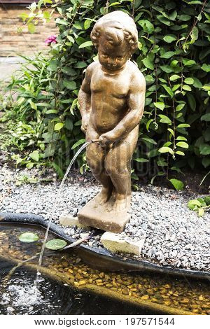 A bronze statue of a boy in the garden