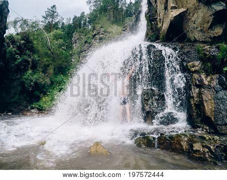 Man in Kamyshlinskiy vodopad waterfall summer, mountains Altai, Russia.