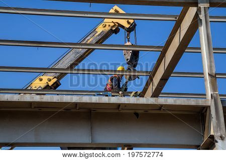 Worker High Above Dissembling Metal Structure