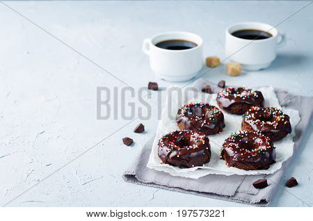 Baked chocolate doughnuts with chocolate glaze on a grey background