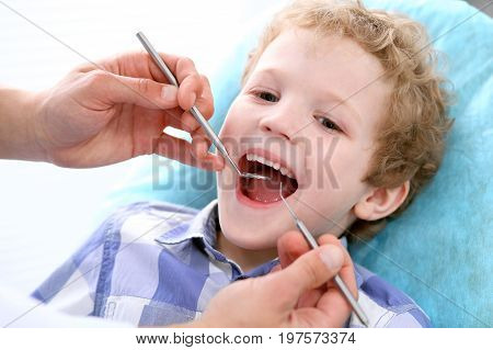 Close up of boy having his teeth examined by a dentist. Medicine and health care