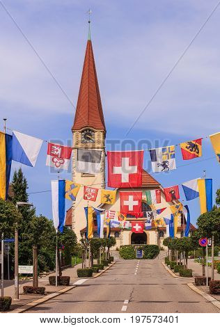 Wallisellen, Switzerland - 30 July, 2017: Kirchstrasse street decorated with flags for the upcoming Swiss National Day, the protestant church in the background. Wallisellen is a town in the Swiss canton of Zurich.