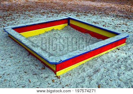 A colored wooden sandbox with gray sand on the playground