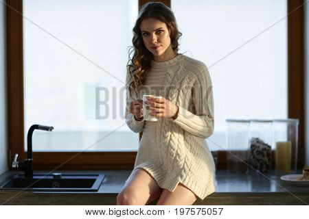 Portrait of a woman holding a cup of tea in her kitchen.
