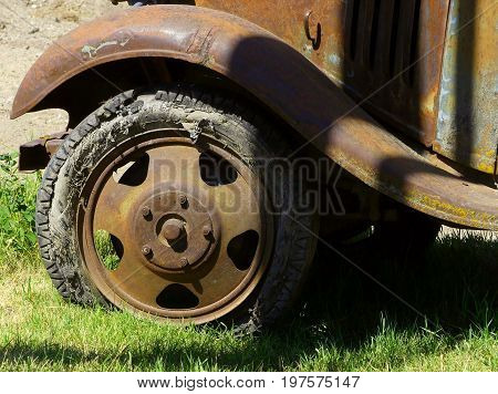 The front fender and wheel off of a vintage truck in need of a new tire.