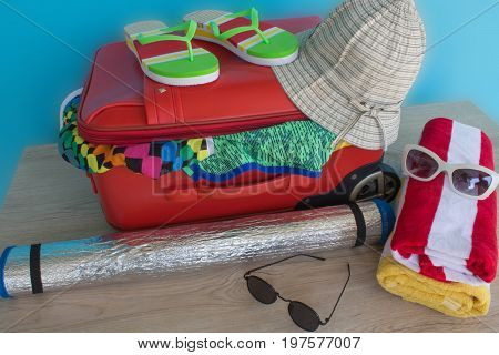 Open red suitcase packed for travelling close up. Suitcase with different things prepared for travel