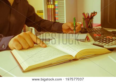 close up businessman hand using pen for writing data information on paperwork concept. A businessman doing some paperwork using his calculator - Retro color