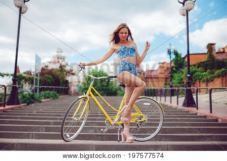 Sexy female model with a yellow grand on the background of the city. Pretty sexy looker young girl in summer shorts posing, smiling and have fun.