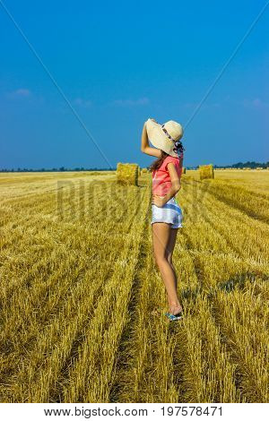 Happy woman on hay stack in sunny day. Beauty romantic girl outdoors against hay stack