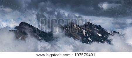 Peaks of ridge Abushura Akhuba jutting out from of cloud. Caucasus mountains. Karachay-Cherkessia. Russia.