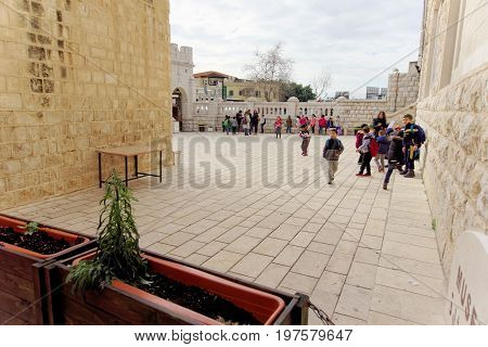 Nazareth Israel. - February 17.2017. Greeck ortohodox church of the Annunciation. A group of local schoolchildren are waiting in the courtyard for the premises of the temple.
