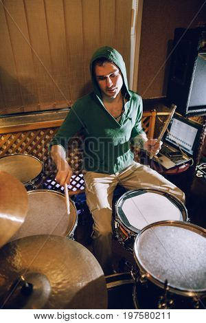 Drummer playing on drum set in recording studio. Music band rehearsal before live concert