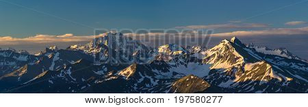First rays of raising sun on mountain peak. Mounts Zakzan-Syrt and Pshish. Greater Caucasus Mountain Range. Karachay-Cherkessia. Russia.