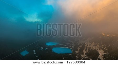 Azgara mountain lakes in last beams of sun. Top view through clouds. Caucasus mountains. Karachay-Cherkessia. Russia.
