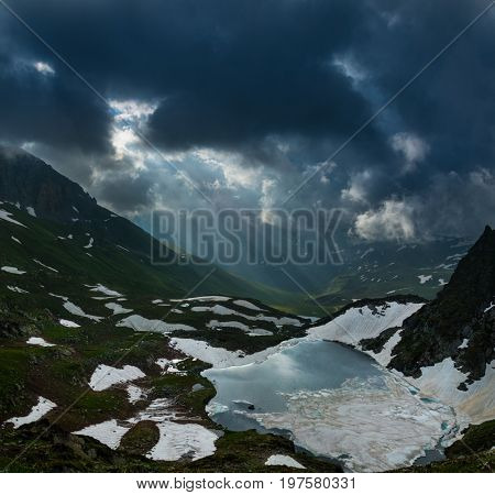 Rising sun is breaking through clouds over Azgara valley and mountain lake. Dramatic overcast sky. Caucasus mountains. Karachay-Cherkessia. Russia.