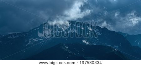 Mountain peak covered by snow at cloudy day. Landscape in blue tone. Greater Caucasus Mountain Range. Karachay-Cherkessia. Russia.