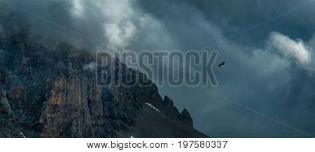 Eagle soaring near rock Zagedan. Dramatic overcast sky. Caucasus mountains. Karachay-Cherkessia. Russia.