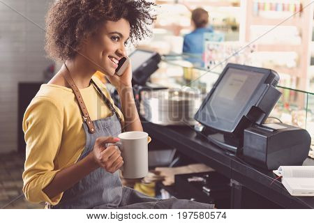 Time for coffee. Cheerful young waitress is talking to her friend on mobile phone and drinking espresso while having short break in small store with organic products. Copy space in the right side