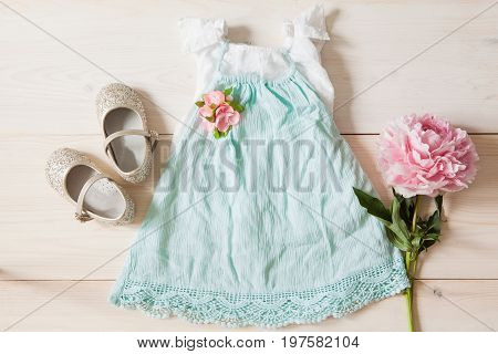 Girl's dress floral tiara and shiny shoes on a wooden background. Girl's apparel for party top view