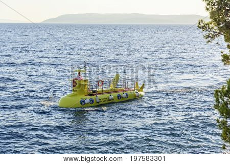 MAKARSKA RIVIERA, CROATIA - 5 JULY, 2017: Walking Yellow submarine sailing on the waves of the Adriatic Sea.
