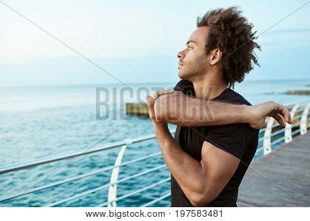 Sports, fitness and healthy lifestyle. Fit Afro-American man runner looking concentrated while stretching his arms by the sea, doing arm and shoulder stretch exercise, standing on pier and looking at the sea. Male jogger warming up before morning workout